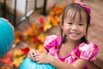 child with teal pumpkin
