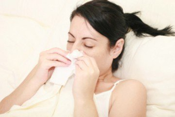 Woman With Cold Sneezing Into Tissue