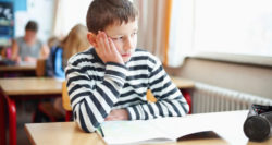 child at desk looking bored