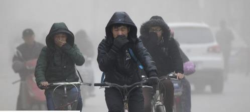 People riding bikes in a Chinese city and covering their mouths because of the terrible air pollution
