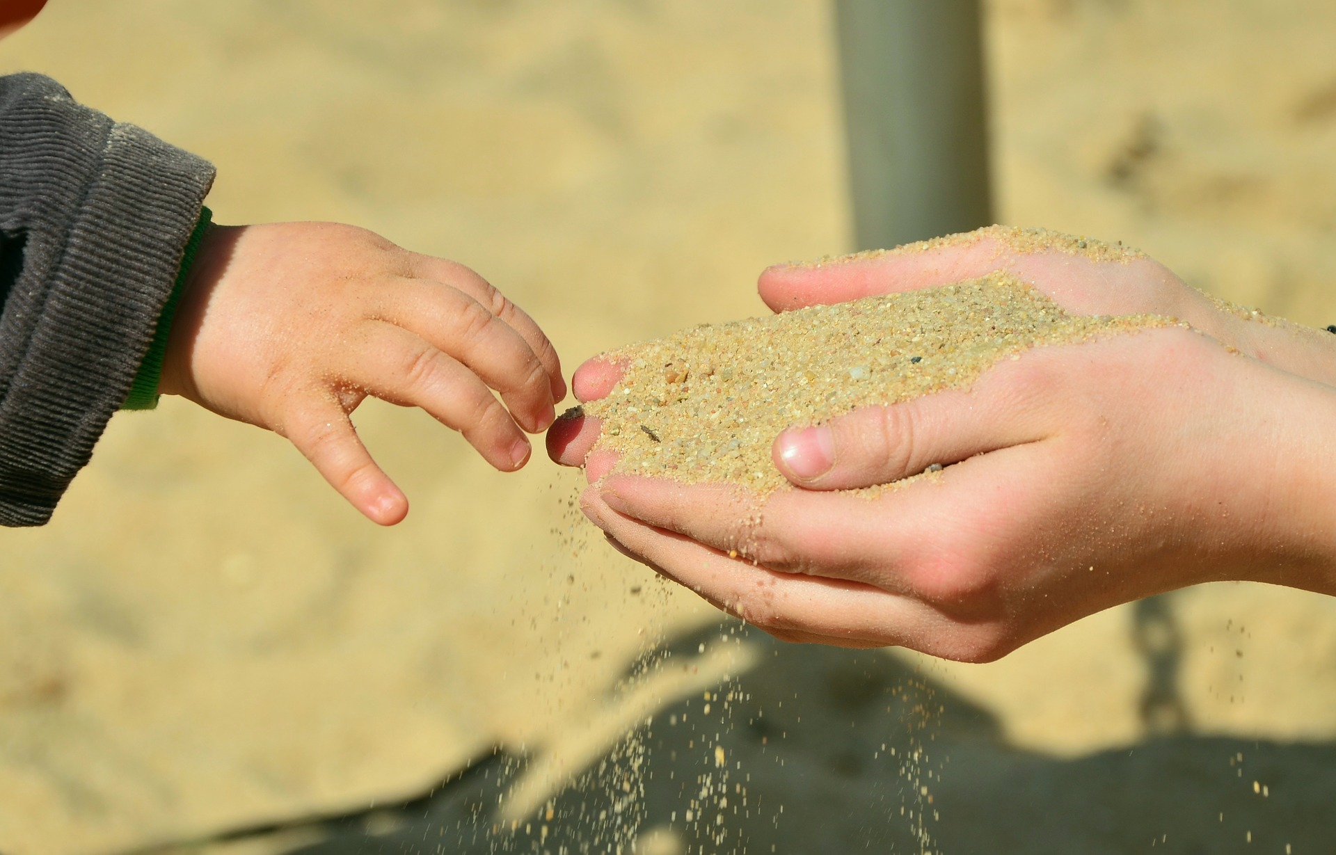 mother's hands holding out sand to child
