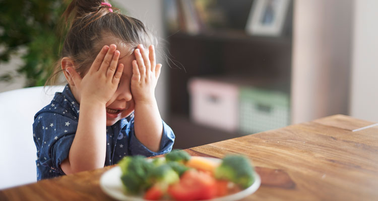 child covering her eyes in front of plate of veggies