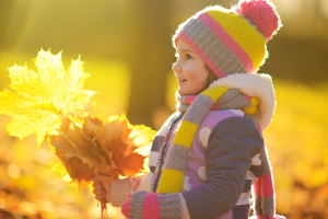 child holding fall leaves