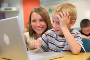 Elementary school student and teacher look at computer