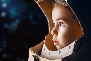 young girl in cardboard astronaut helment