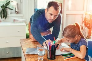 father helping his daughter with homework