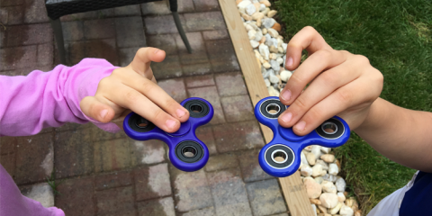 Child hands each holding a fidget spinner