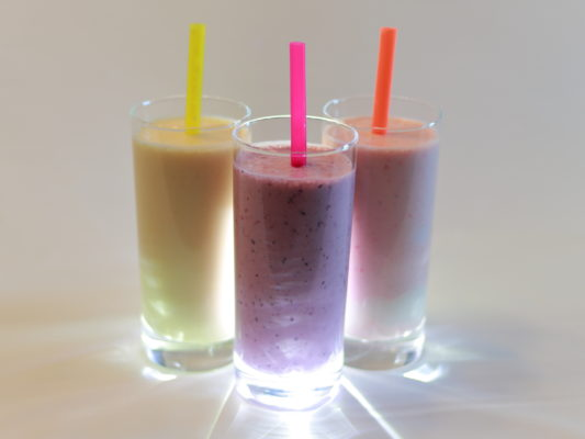 three smoothies in glasses with straws