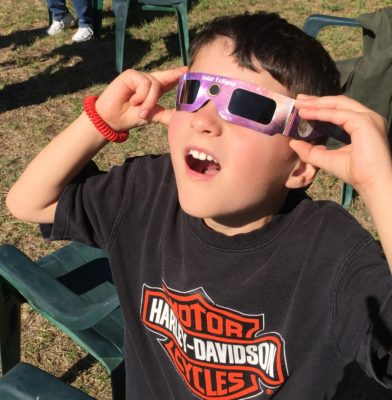 child wearing eclipse glasses looking surprised