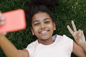 Smiling girl taking selfie on her smartphone
