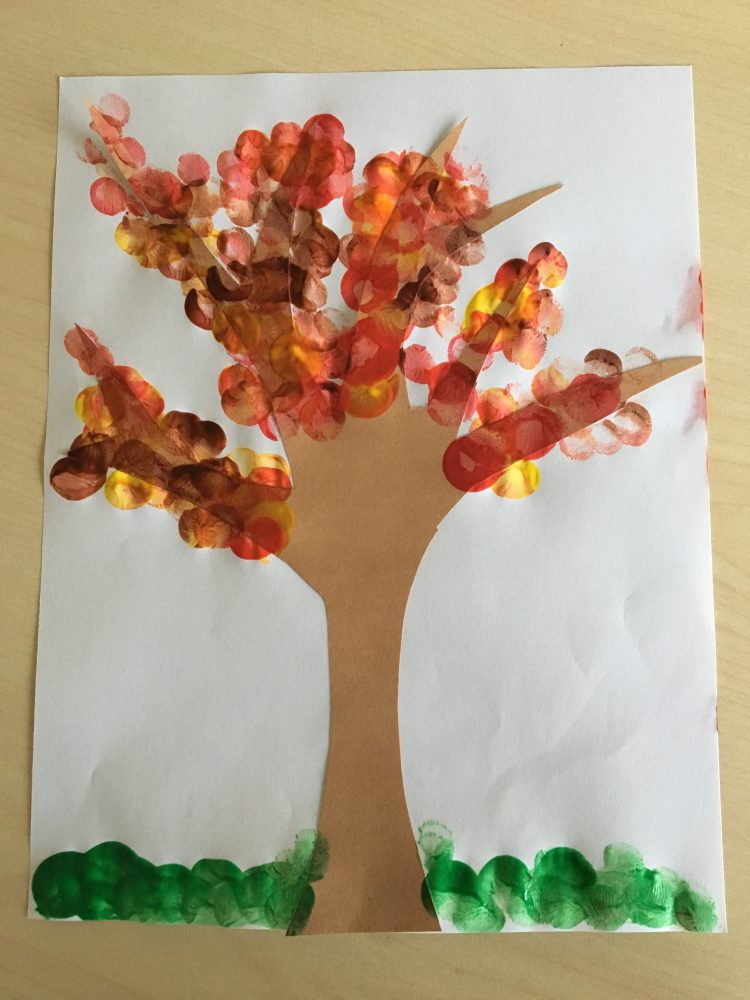 Tree cutout with colorful finger paint to serve as leaves
