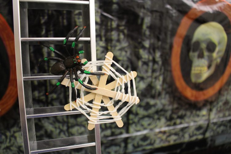 Spider web made out of Popsicle sticks and white rubber bands with a spider attached