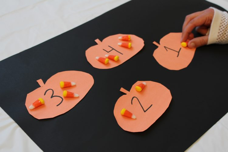 Numbered orange pumpkin paper cut-outs with varying amounts of candy corn on each cut-out