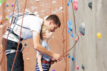 little boy preparing to climb rock wall