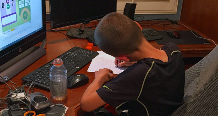 child sitting at desk with a computer