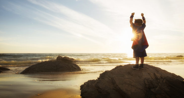 child at beach with hands up overcoming obstacles in life