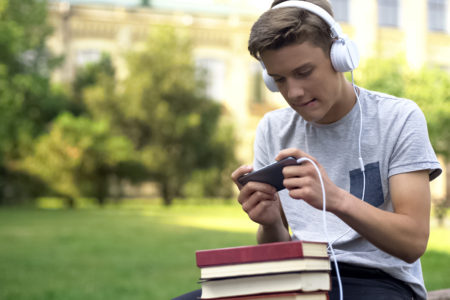 boy procrastinating by listening to music holding books