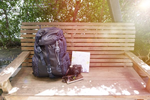 Backpack with travel map and camera