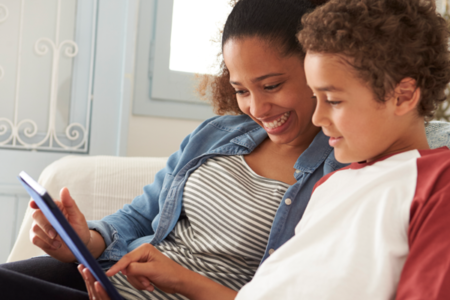 mother and son looking at computer tablet together