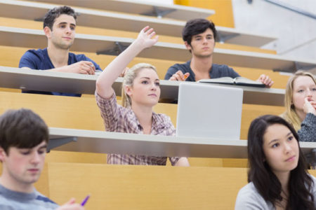students hand raised in college lecture hall