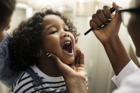 doctor looking in little girl's mouth