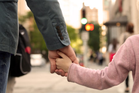 father holding daughters hand, walking to school