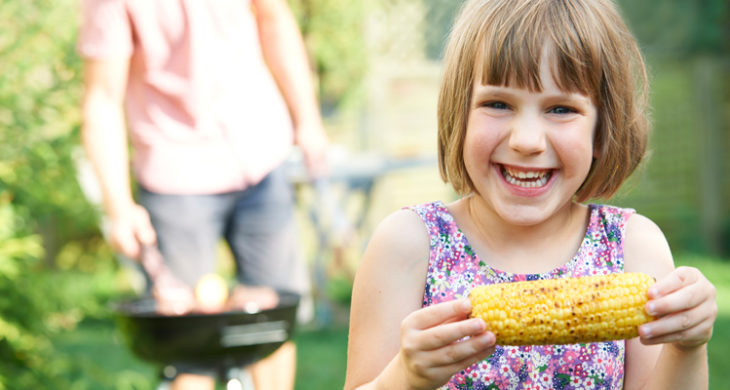 Girl eating corn on the cobb