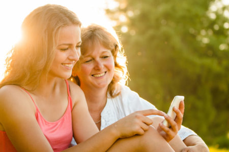 mom and teen looking at cell phone