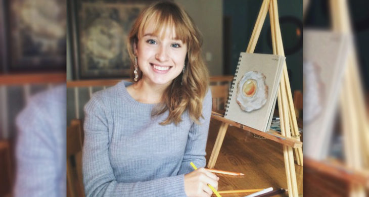 Lexie next to her artwork on an easel.