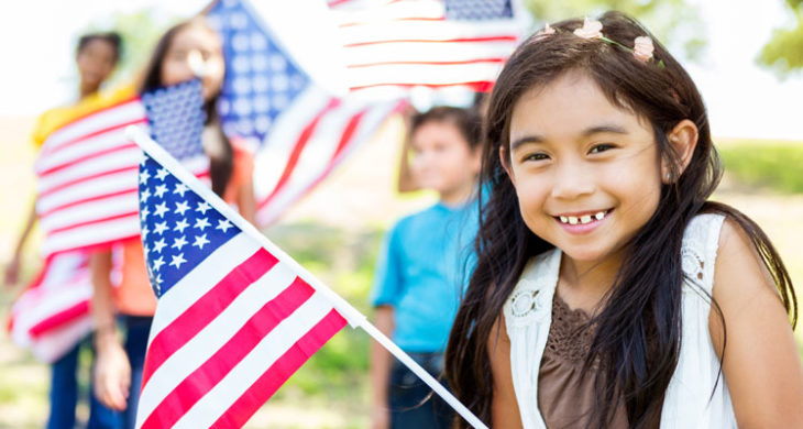 little girl holds American Flag