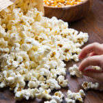 Hands of children eating popcorn