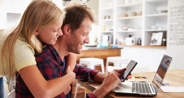 father and daughter looking at phone and laptop