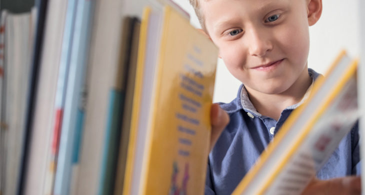 young boy looking at books on a bookshelf