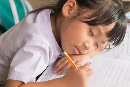 girl sleeping, doing homework