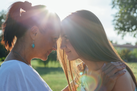 Daughter with mother hugging at sunset