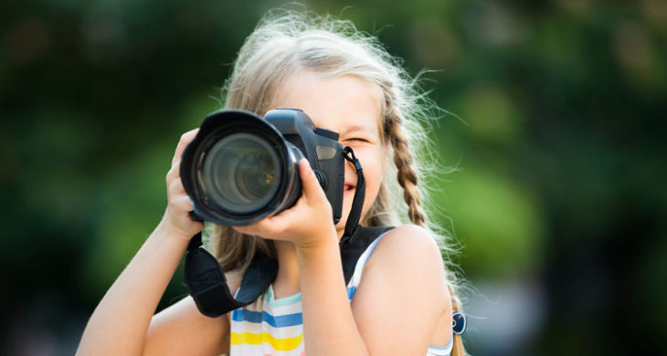 kid with camera taking nature photos