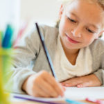 Child writing with pencil at desk