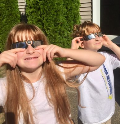 two kids wearing eclipse glasses