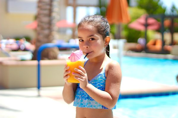 girl by the pool with a smoothie