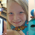 child with eclipse glasses, girl with butterfly and boy in museum with a suspended ball