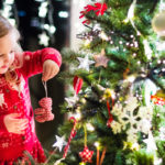 little girl hanging an ornament on Christmas tree