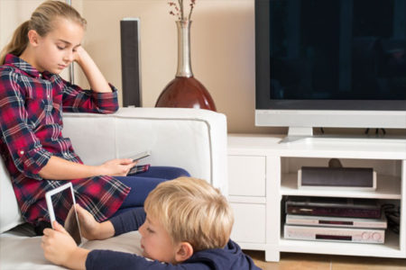 siblings using phone and tablet in livingroom