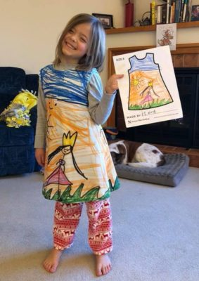 child holding artwork and wearing dress with same art