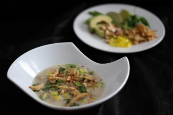 Bowl of chicken and rice soup with garnishes