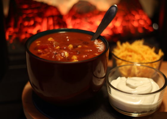 Bowl of chili in front of a fire