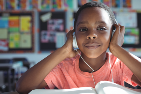 child wearing headphones while studying in class