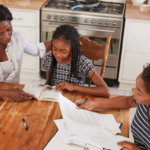 mom helping two daughters schoolwork at kitchen table