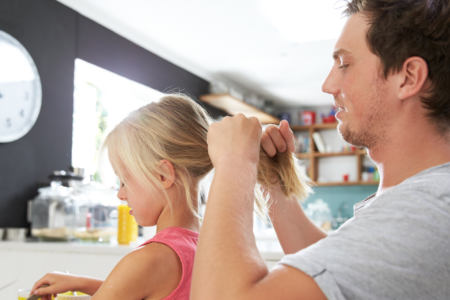 Father Styling Daughter's Hair At Breakfast Table