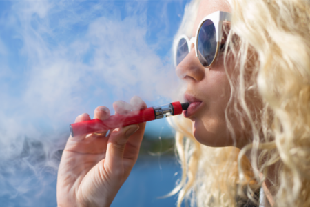 female teen smoking a vape pen