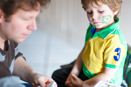 Dad painting flag on face of little kid for soccer